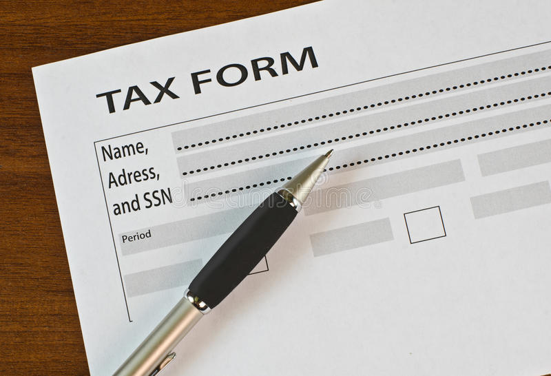 The filling in of paper documentation. On a wooden table is the income tax return form and fountain pen stock photography