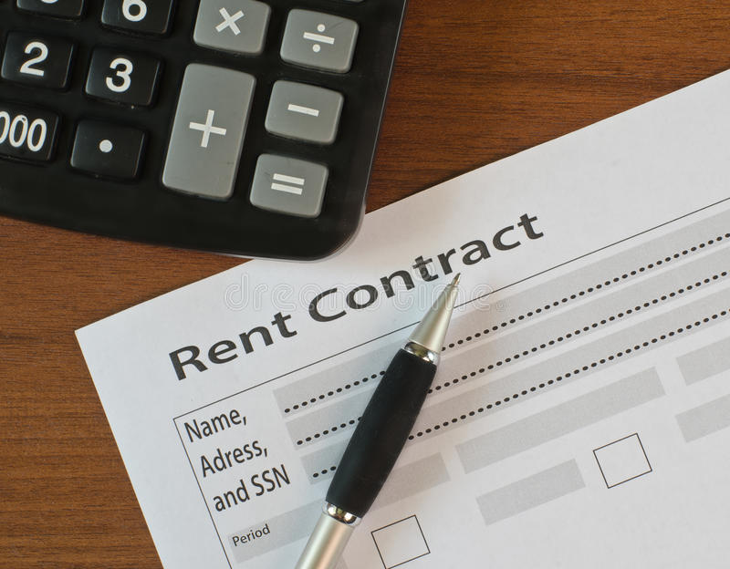 The filling in of paper documentation. On a wooden table lies blank rent contract and pen royalty free stock image