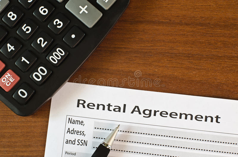 The filling in of paper documentation. On a wooden table lies blank rental agreement and pen stock images
