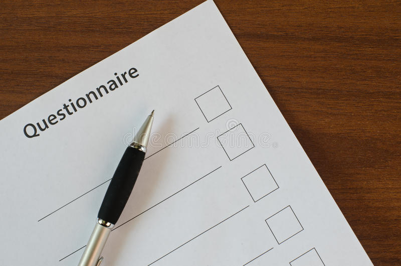 The filling in of paper documentation. On a wooden table lies in the questionnaire and pen stock photos