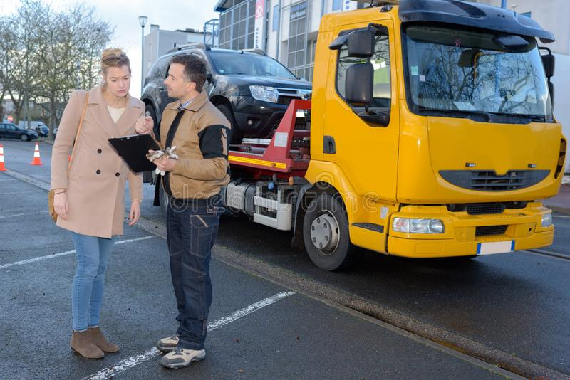Filling papers before towing car. Filling papers before towing a car royalty free stock photo