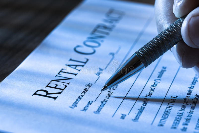 Filling rental agreement form. Close-up Of A Person Filling Rental Agreement Form With Pen royalty free stock photography