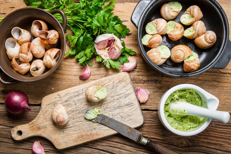 Filling snails with garlic butter stock photography