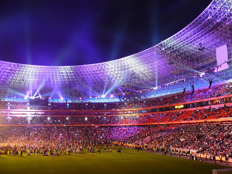 Filling soccer fans nightly Donbas arena. Beautiful night football stadium and light rays stock photos