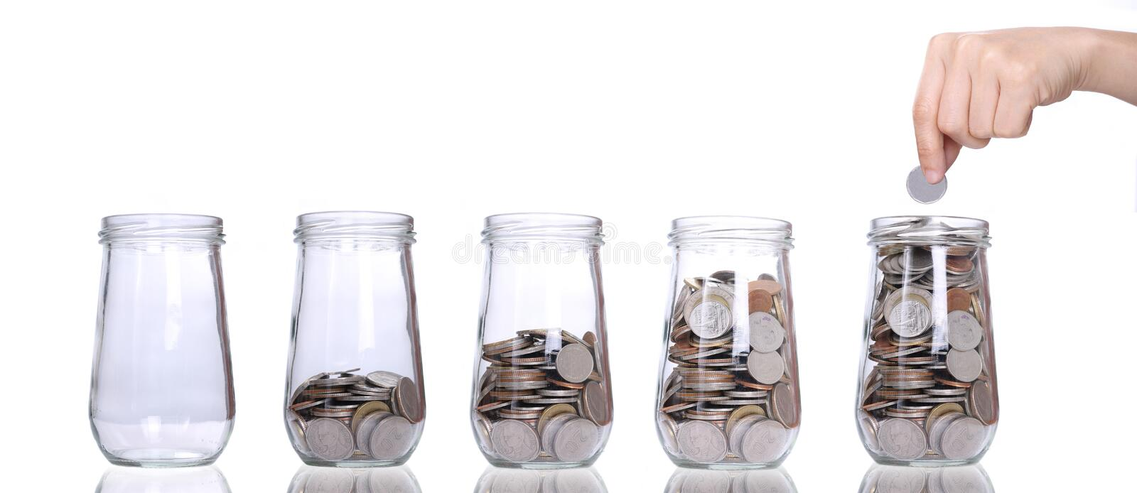 Filling up coins to empty glass royalty free stock image