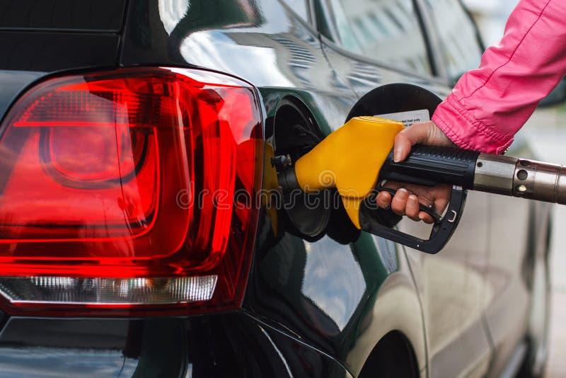 Filling up at petrol station. Woman filling up car at petrol station, black car stock photography
