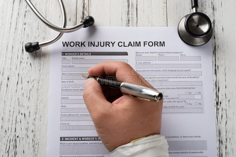 Filling up work injury claim form by a wrapped hand with stethoscope nearby medical and insurance concept. Filling up a work injury claim form by a wrapped hand stock images