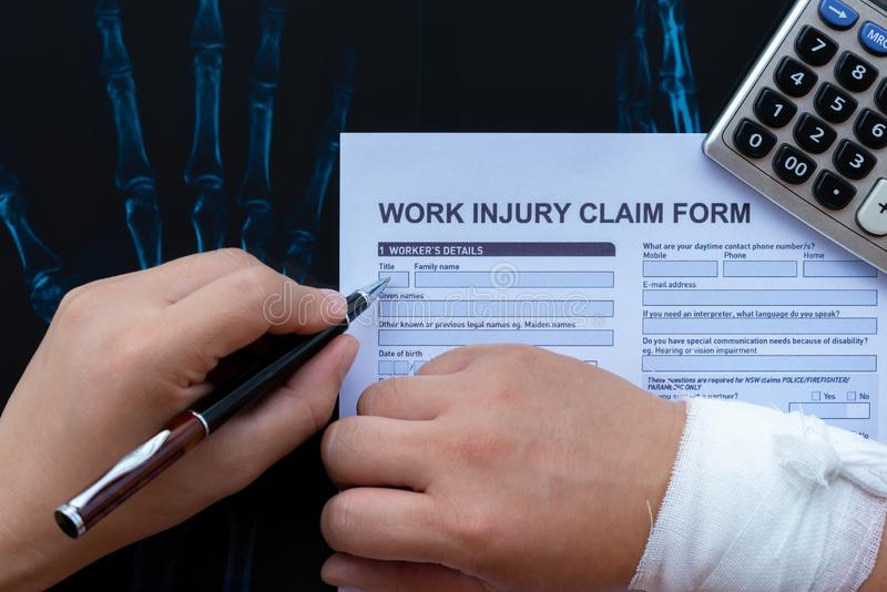 Filling up a work injury claim form with a wrapped hand on top of an X-ray film stock image