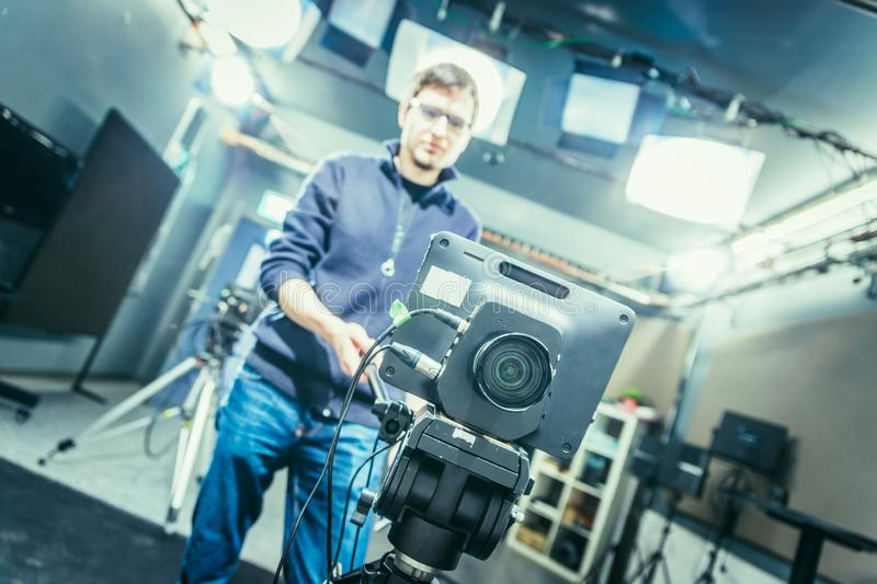 Film camera in broadcasting studio, spotlights and equipment, cameraman in the blurry background. Lens of a film camera in an television broadcasting studio stock image