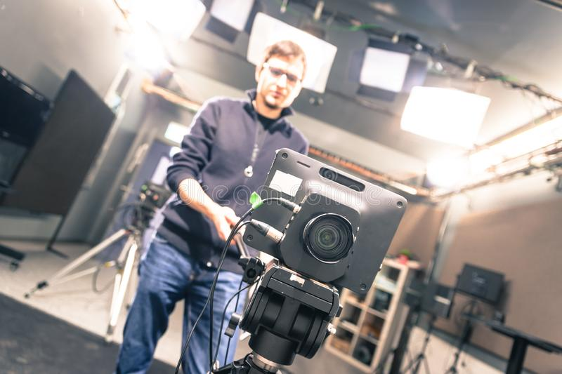 Film camera in broadcasting studio, spotlights and equipment, cameraman in the blurry background. Lens of a film camera in an television broadcasting studio stock photos