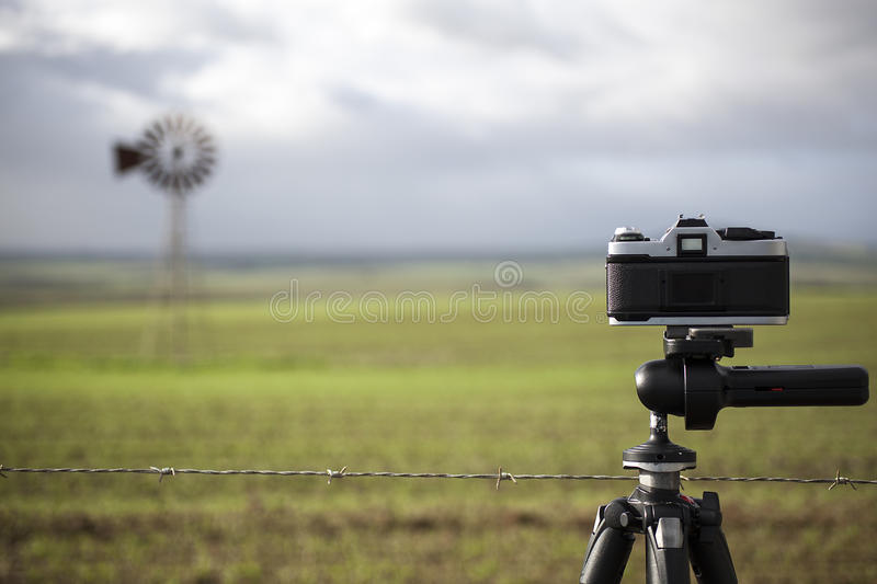 Film camera on tripod photographing landscape scene stock photos