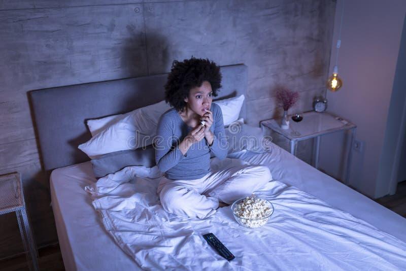 Film d'horreur de observation de femme ? la TV photographie stock libre de droits