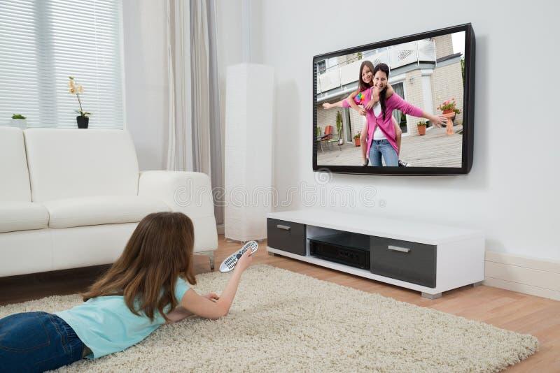 Film de observation de fille à la télévision images stock