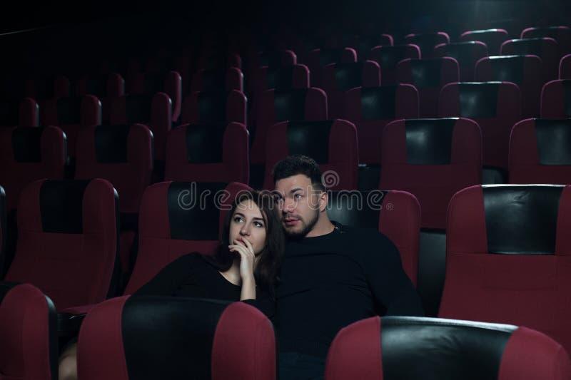 Film de observation de sourire heureux de couples dans le théâtre images stock