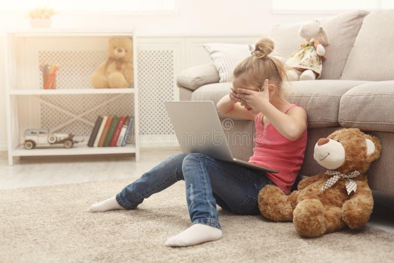 Film de observation occasionnel effrayé de petite fille sur l'ordinateur portable tout en se reposant sur le plancher à la maison images libres de droits