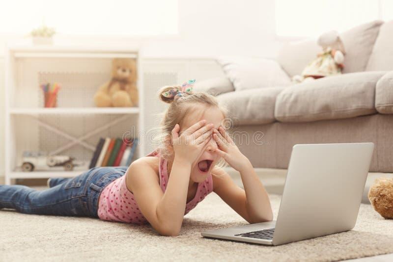 Film de observation occasionnel effrayé de petite fille sur l'ordinateur portable tout en se trouvant sur le plancher à la maison photos stock