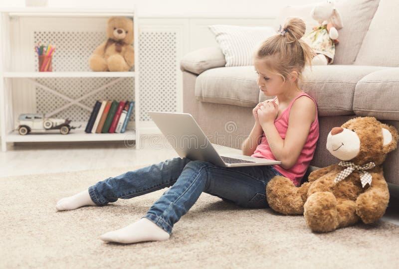 Film de observation triste de petite fille sur l'ordinateur portable photo libre de droits