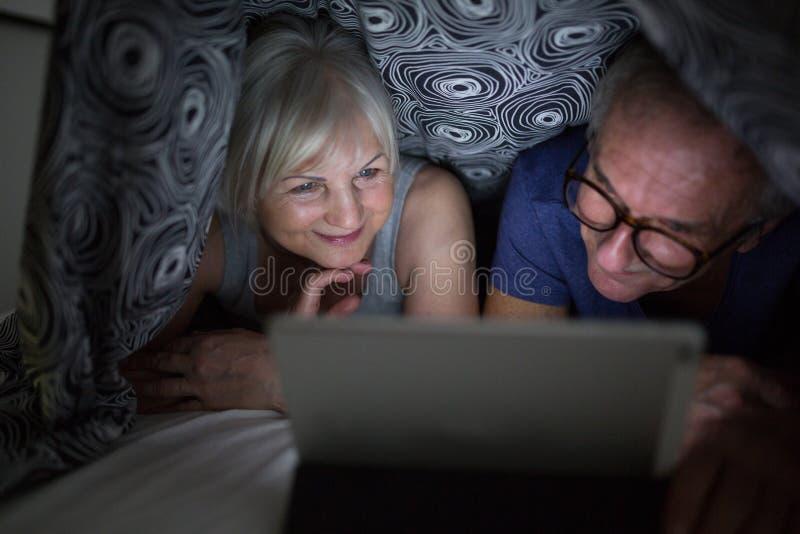 Film di sorveglianza della gente senior felice sotto la trapunta immagine stock libera da diritti
