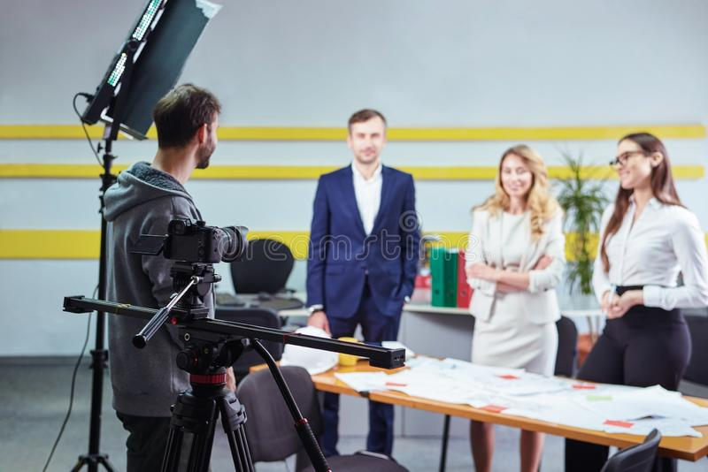 Film director discussing movie plan with the actors. In the office scene. Lights pointing to the actors stock photography