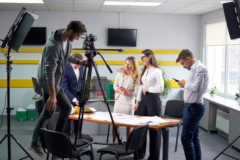 Film director discussing movie plan with the actors. In the office scene. Lights pointing to the actors royalty free stock photos