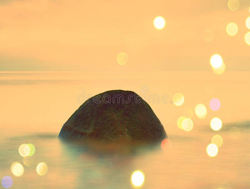 Film effect. Long exposure of sea and big boulders sticking up from water within twilight time. Pink sunset at rocky coast of Bals. Film grain effect. Long royalty free stock photography