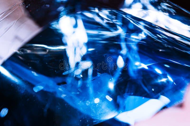 Film froissé en plastique olographe avec des réflexions de la lumière du soleil de contraste Tons bleus avec les ombres noires fo photographie stock libre de droits