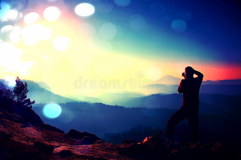 Film grain. Professional photographer takes photos with mirror camera on peak of rock. Dreamy fog. Film grain effect. Professional photographer takes photos with royalty free stock photography