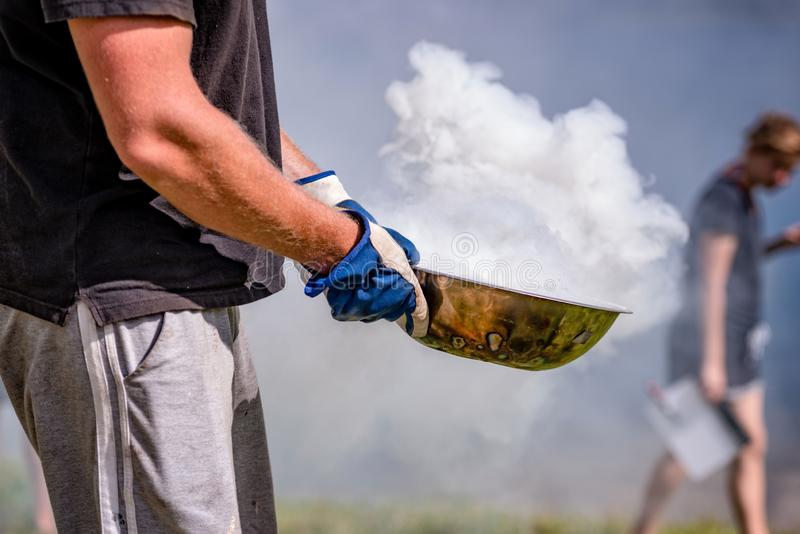 Film industry. Man brings spewing smoke dish.  royalty free stock images