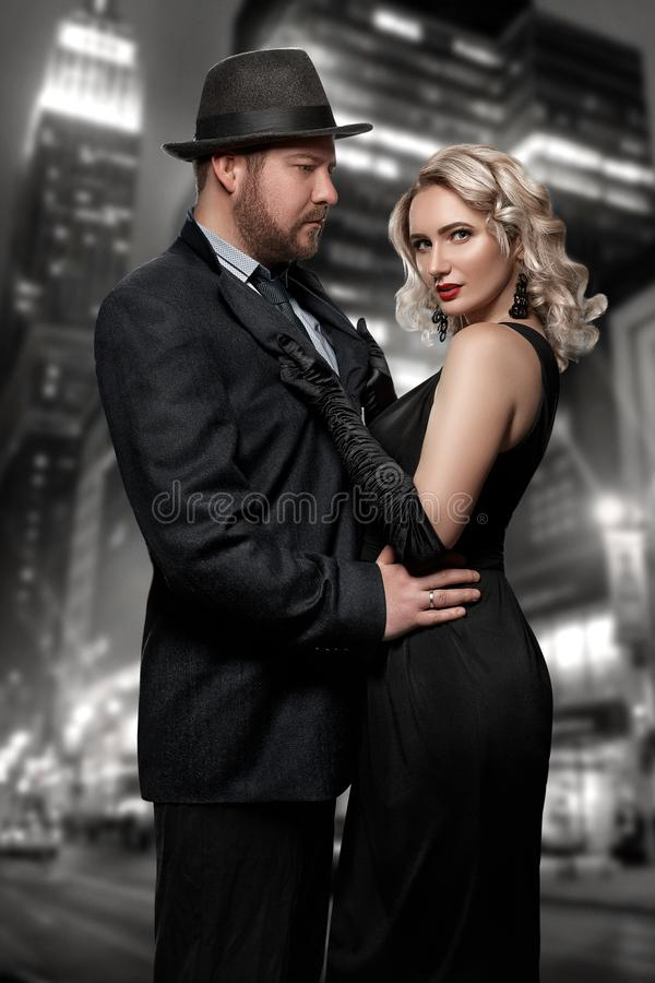 Film noir. Detective man in a raincoat and hat and a dangerous woman with red lips in black dress. Couple stands against stock image