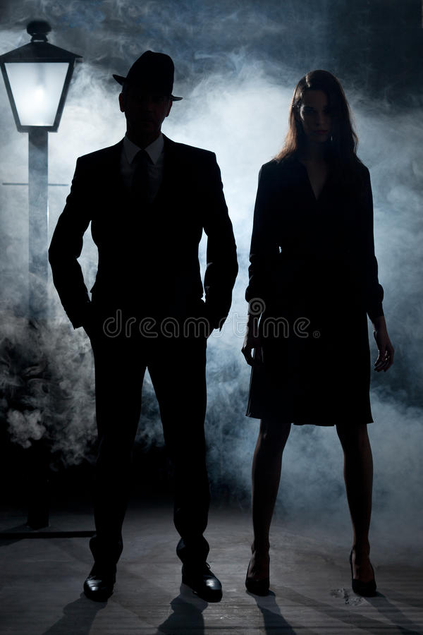 Film noir gangster couple street light mist. Man and girl in cinema noir gangster style. They are standing in the mist or fog with a lantern pole or lamppost stock photos