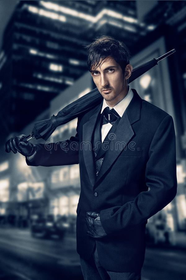 Film noir. Retro style fashion portrait of a killer. A man in a suit with an umbrella in his hand against a background royalty free stock images