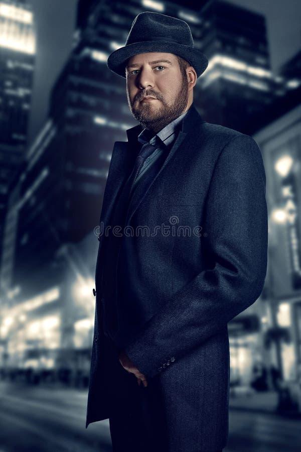 Film noir Retrostilmodeporträt eines Detektivs Ein Mann in einer Klage gegen einen Hintergrund einer Nachtstadt stockbilder