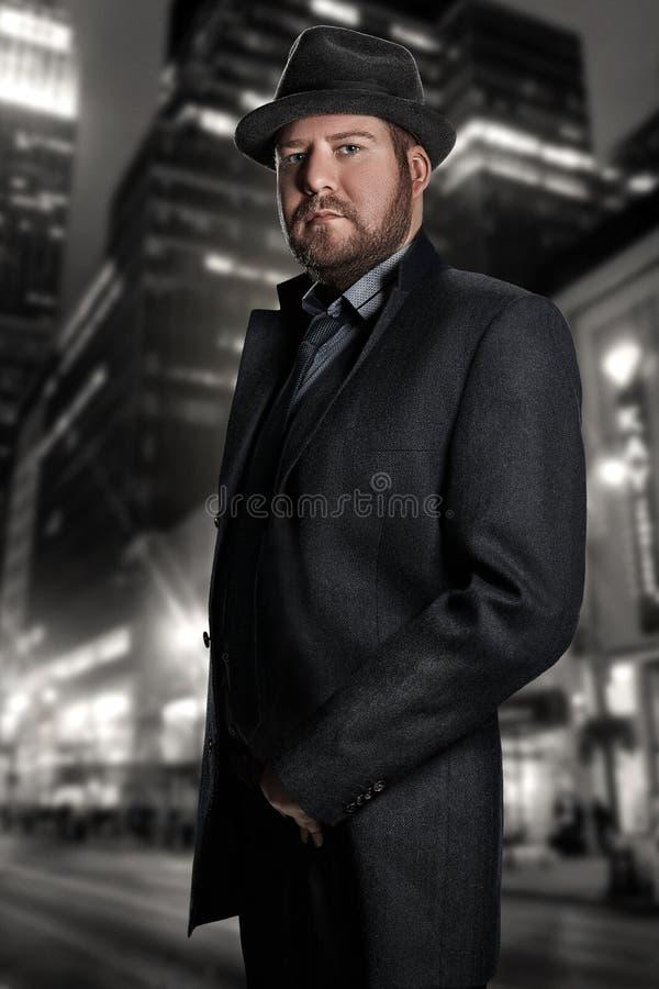 Film noir Retrostilmodeporträt eines Detektivs Ein Mann in einer Klage gegen einen Hintergrund einer Nachtstadt lizenzfreies stockbild