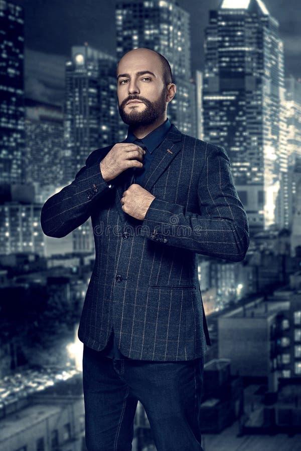 Film noir Retrostilmodeporträt eines Detektivs oder des Mörders Ein Mann in einem Anzug justiert seine Bindung gegen den Hintergr stockbilder