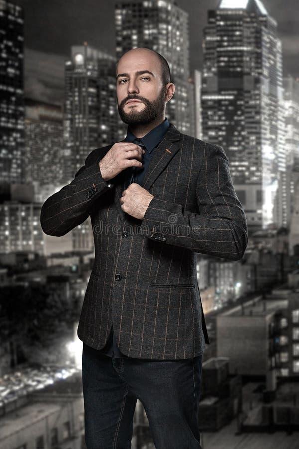 Film noir Retrostilmodeporträt eines Detektivs oder des Mörders Ein Mann in einem Anzug justiert seine Bindung gegen den Hintergr stockfotos
