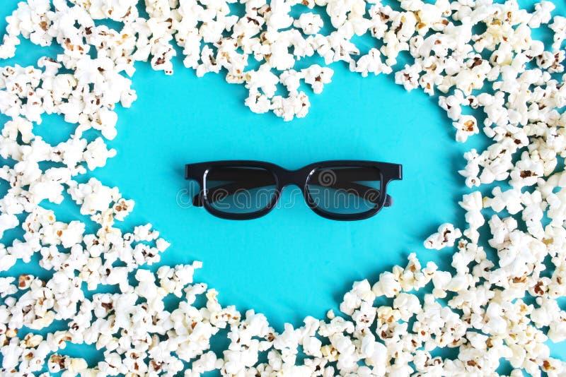 Film, passatempo, spettacolo e cinema di amore di concetto Forma del popcorn di cuore e di vetri 3d su fondo blu fotografia stock