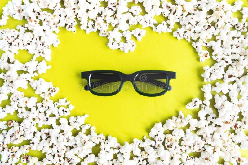 Film, passatempo, spettacolo e cinema di amore di concetto Forma del popcorn di cuore e di vetri 3d su fondo giallo fotografia stock libera da diritti