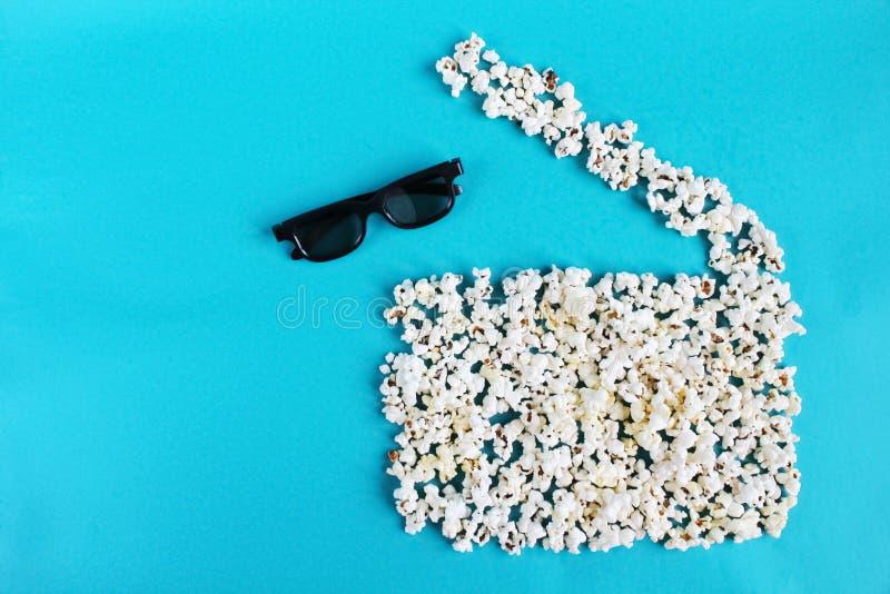 Film, passatempo, spettacolo e cinema di amore di concetto Valvola di film del popcorn e vetri 3d su fondo blu fotografie stock