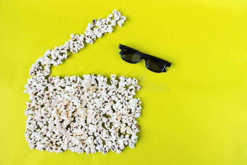Film, passatempo, spettacolo e cinema di amore di concetto Valvola di film del popcorn e vetri 3d su fondo giallo immagine stock