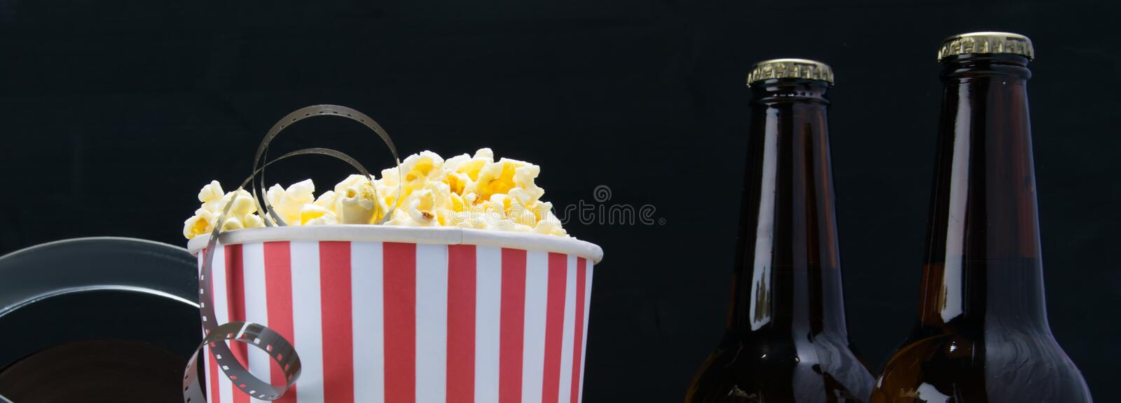 Film in popcorn, on a black background, with two bottles of beer royalty free stock photo