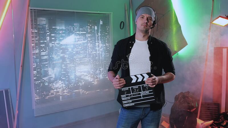 Film producer assistant smiling to the camera. Medium shot of film producer assistant smiling to the camera and giving action with movie clapper board royalty free stock photo