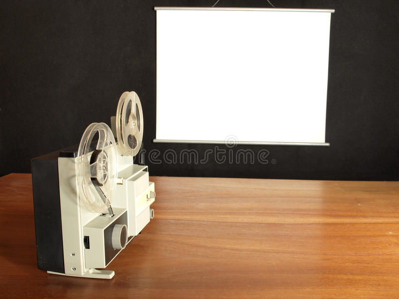 Film projector. Aimed at the screen hangs on a black wall royalty free stock photo