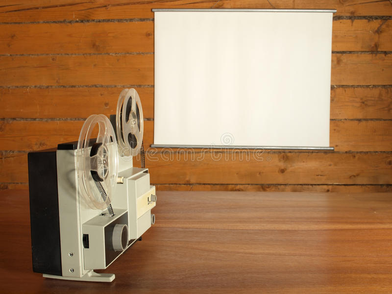 Film projector. Aimed at the screen hanging on the log wall royalty free stock images