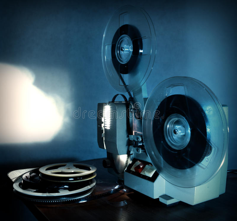 Film Projector. Old 8mm film projector showing the film in dusk onto a wall beside a stack of film reels stock photography