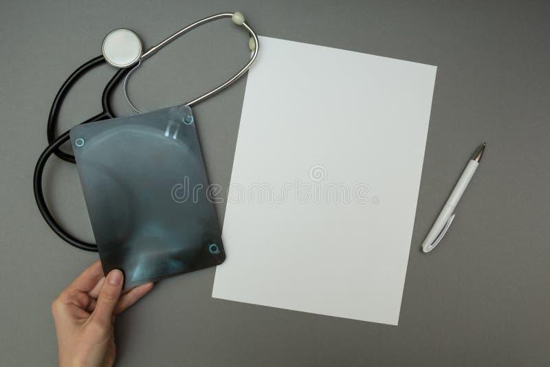 Film radiographique dans les mains d'un docteur, un concept sur un fond gris photos libres de droits