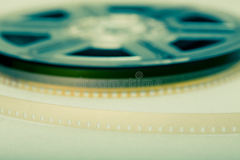 Film reel. In background and focus on film. Movie industry symbol stock photo