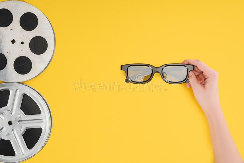 Film reels and female hand holding stereoscopic 3d glasses isolated royalty free stock photos