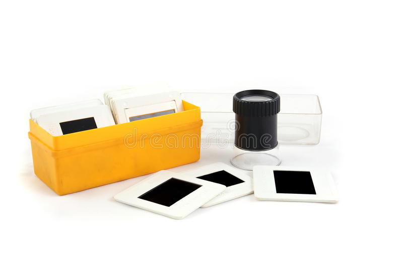 Film slide inspector tool. Photo editing magnifier loupe over stack of old transparency film royalty free stock photo