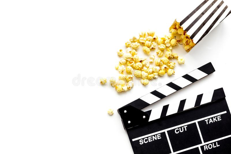 Film watching concept. Clapperboard and popcorn on white background top view copy space. Film watching concept. Clapperboard and popcorn on white background top royalty free stock photography