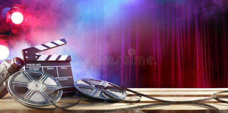 Filma filmbakgrund - Clapperboard och filmrullar royaltyfri fotografi